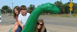 Mother and kids with a dinosaur roadside attraction